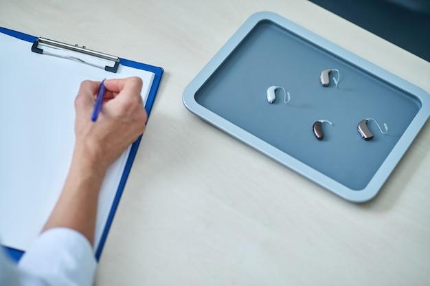 Scrittura a mano su taccuino e selezione di apparecchi acustici