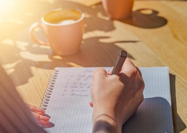 Piani di scrittura a mano in taccuino o pianificatore su tavolino da caffè in legno con luce solare dalla finestra e caffè ...