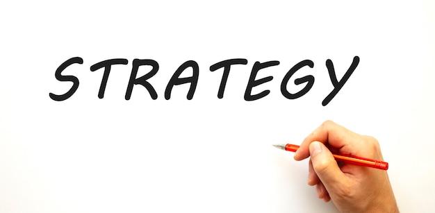 Mano che scrive strategia con la penna. isolato su sfondo bianco. concetto di affari.