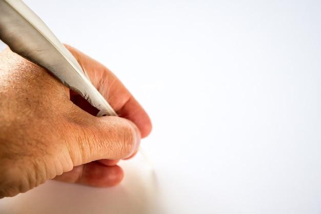 Scrittura a mano con una piuma di uccello isolata su sfondo bianco