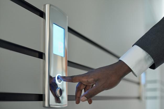 Mano del giovane uomo d'affari africano in abiti da cerimonia premendo il pulsante sulla parete per catturare l'ascensore all'interno del centro business
