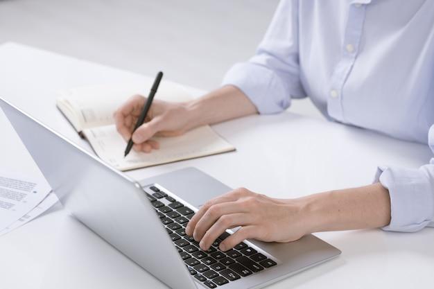Mano di giovane donna di affari che spinge i tasti della tastiera del computer portatile mentre prende appunti in taccuino dal posto di lavoro
