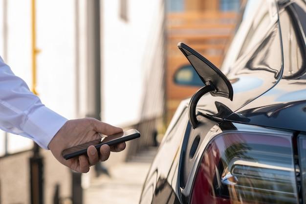 Mano del giovane contemporaneo con lo smartphone davanti all'auto elettrica