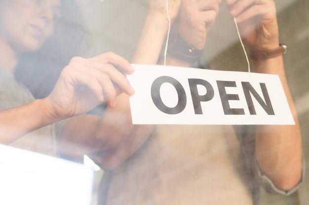 Mano di giovane femmina che tiene avviso di carta che annuncia aperto mentre suo marito lo appende alla porta del loro ristorante o bar