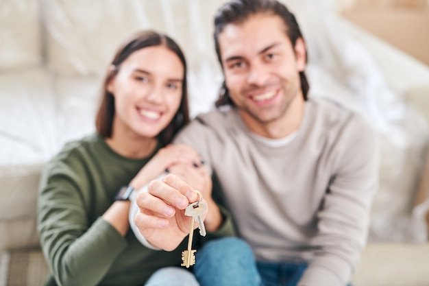 Mano del giovane maschio che tiene la chiave dal nuovo appartamento o casa e sua moglie seduta vicino mentre entrambi seduti