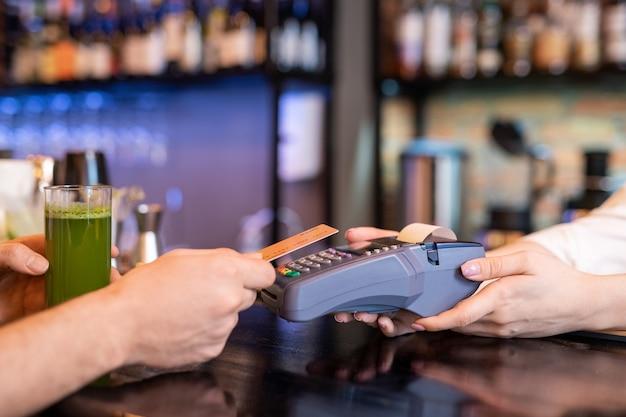 Mano del giovane che tiene la carta di plastica sopra la macchina di pagamento tenuta dalla cameriera mentre paga per un bicchiere di frullato di verdure fresche
