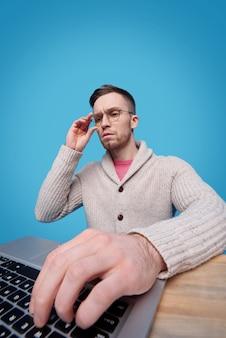 Mano di giovane uomo d'affari serio sulla tastiera del computer portatile durante la ricerca online di informazioni necessarie per un nuovo progetto di business