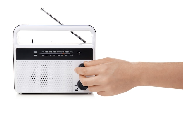 Mano di giovane donna con ricevitore radio retrò su superficie bianca