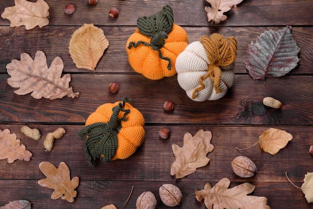 Natura morta autunnale artigianale: zucche e foglie lavorate a maglia su uno sfondo di legno
