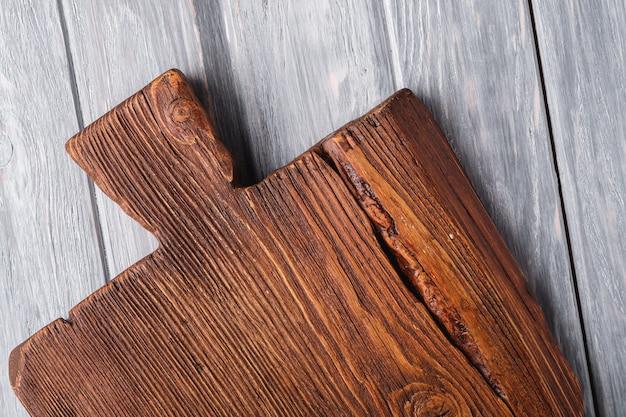 Vecchio tagliere artigianale in legno marrone scuro Foto Premium
