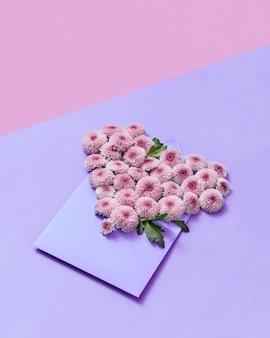 Busta artigianale con cuore di fiori di crisantemo resistente su uno sfondo pastello bicromia, copia dello spazio. carta di congratulazioni.