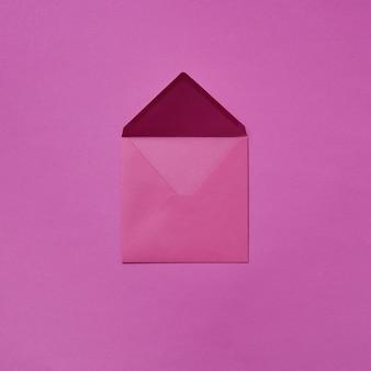 Busta aperta artigianale per cartolina di congratulazioni su uno sfondo magenta con spazio di copia. lay piatto