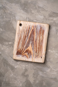 Vecchio tagliere di legno artigianale su sfondo di cemento di pietra, vista dall'alto
