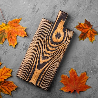 Vecchio tagliere di legno artigianale con foglie di autunno su sfondo concreto, vista dall'alto