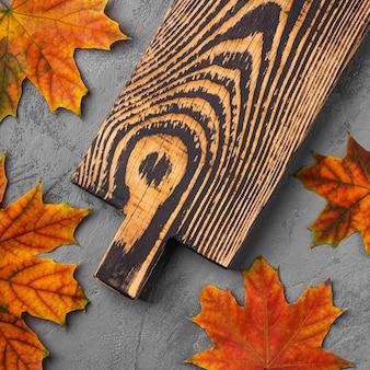 Vecchio tagliere di legno artigianale con foglie di autunno su cemento