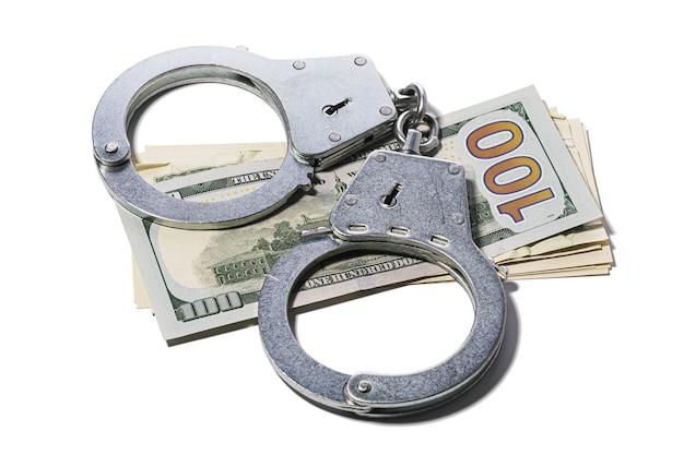 Manette su dollari isolati su sfondo bianco concetto sul tema della frode con transazioni in valuta estera