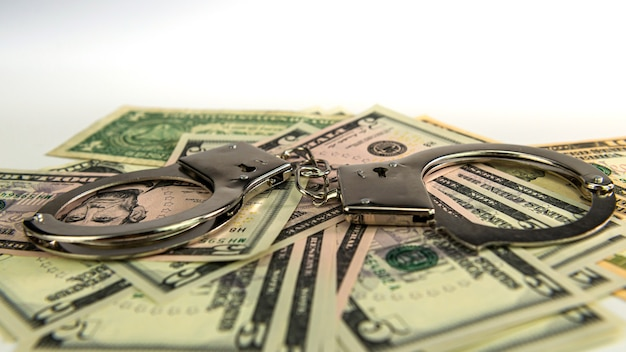 Manette su sfondo di denaro, banconote da un dollaro, corruzione di denaro contante, criminalità finanziaria di denaro sporco e manette di polizia in metallo, messa a fuoco selettiva