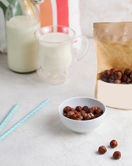 Una manciata di nocciole, close-up di nocciole, accanto a un pacchetto di noci con spazio per testo e logo