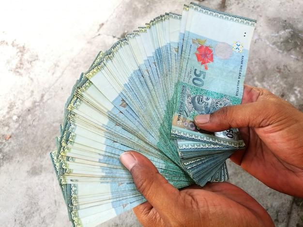 Manciata di banconote malese ringgit mostrando all'aperto su sfondo grigio con texture