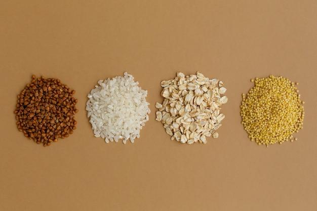 Manciate di vari cereali su sfondo marrone. riso e farina d'avena, grano saraceno e miglio