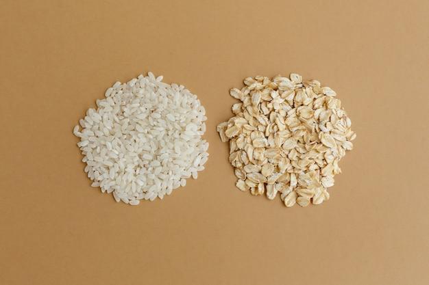 Manciate di vari cereali su sfondo marrone. riso e farina d'avena