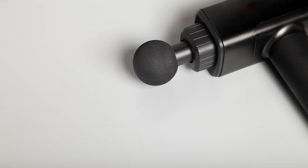 Pistola per massaggio shock terapeutico professionale wireless portatile su sfondo grigio. massaggiatore a percussione dei tessuti muscolari profondi per atleti, rilassa, allevia il dolore. concept sport e stile di vita sano