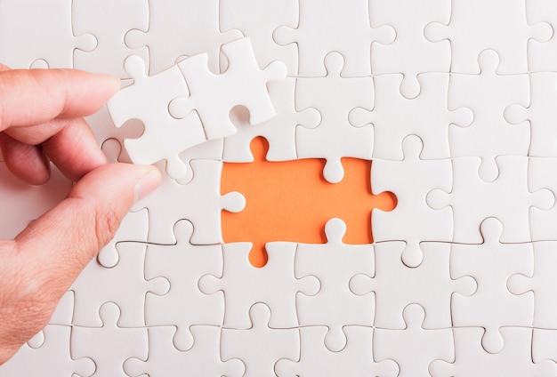 Tenere in mano l'ultimo pezzo di carta bianca gioco di puzzle gli ultimi pezzi messi a posto per risolvere il problema