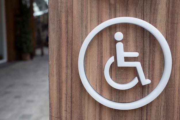 Bagni per disabili dell'etichetta bianca sul pavimento in legno.