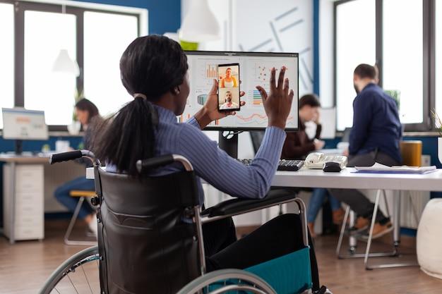 Handicappata disabile imprenditrice afroamericana che saluta il lavoro di squadra remoto durante la conferenza videochiamata online nell'ufficio aziendale di avvio. teleconferenza sullo schermo del telefono