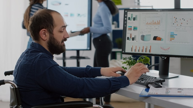 Uomo d'affari disabile disabile in sedia a rotelle che discute con un collega, chiede informazioni digitando sul computer, controlla i dati statistici lavorando in un ufficio commerciale di avvio con un team diversificato