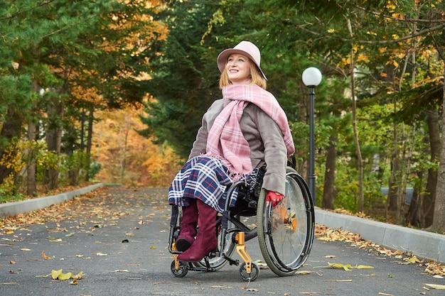 Donna sorridente paralizzata handicappata in sedia a rotelle si muove nel parco d'autunno