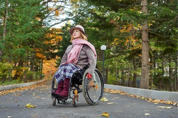 Donna handicappata paralizzata su sedia a rotelle si muove nel parco d'autunno
