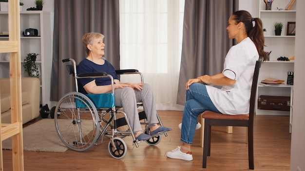 Donna anziana handicappata in sedia a rotelle che parla con l'infermiera femminile. casa di riposo per anziani, assistenza sanitaria, assistenza sanitaria, assistenza sociale, assistenza medica e domiciliare