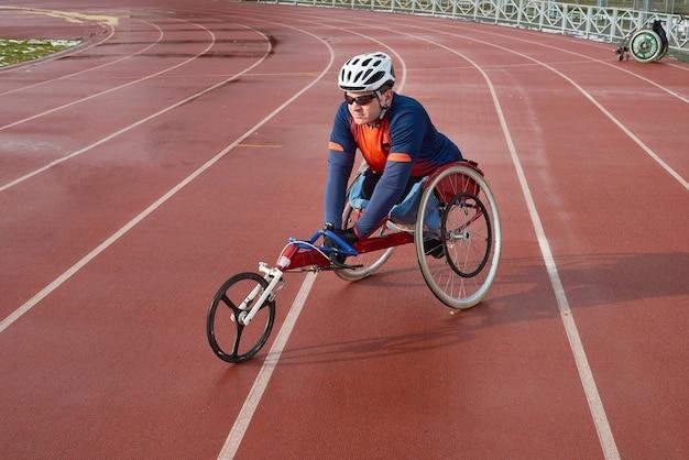 Sportivo disabile in casco e occhiali da sole seduto in sedia a rotelle da corsa allo stadio di atletica leggera all'aperto e si prepara per la maratona