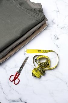 Artigianato, riparazione abbigliamento. accessori per cucire jeans strappati con sfondo colorato dall'alto. lay piatto