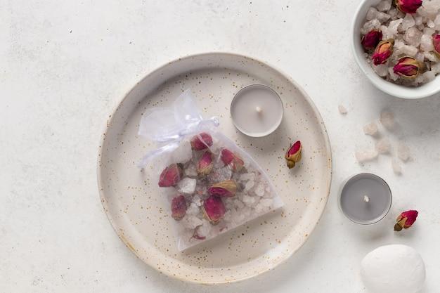 Sale da bagno artigianale con rose ed erbe aromatiche in sacchetto a rete. bustina di tè da bagno. prodotti per aromaterapia fai da te. sfondo bianco