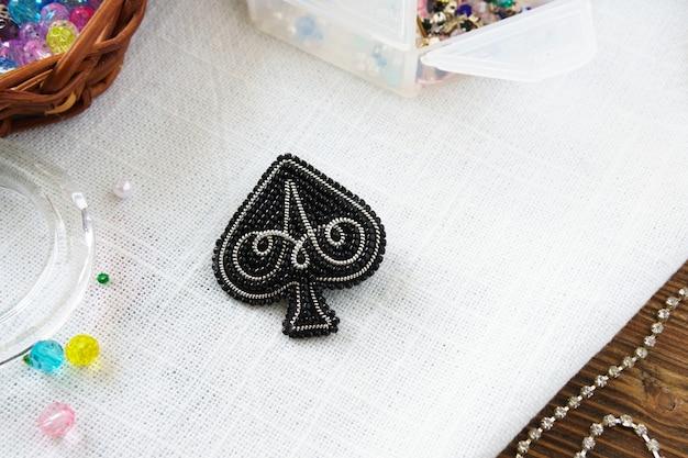 Spilla di perline fatta a mano spades nero sul tavolo su sfondo bianco