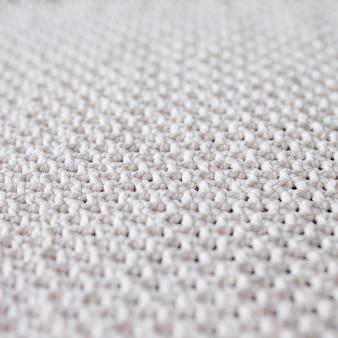 Macrame beige fatto a mano. texture macramè, lavorazione a maglia ecologica e moderna. tappeto macrame sul tavolo di legno