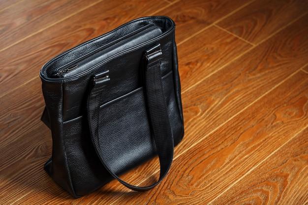 Borsa in pelle nera fatta a mano su fondo in legno, realizzata in materiale naturale.