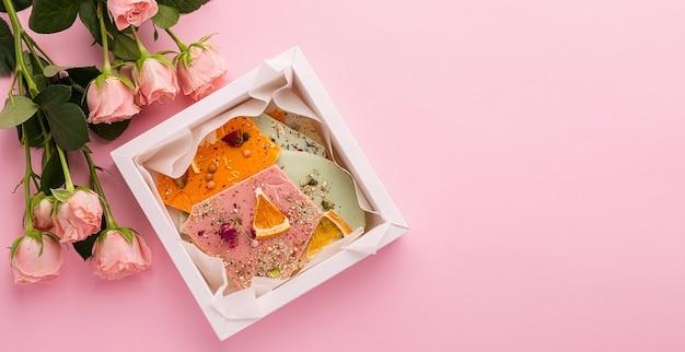 Pezzi di cioccolato fatti a mano di diversi colori su rosa e un bouquet di rose.