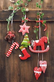 Decorazione natalizia fatta a mano appesa sopra fondo di legno rustico. immagine dai toni nostalgici in stile retrò