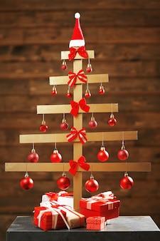 Un albero di natale fatto a mano e regali sullo sfondo della parete in legno