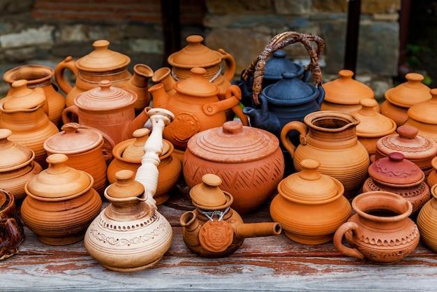 Tazze, pentole e piatti marroni di argilla fatti a mano su un supporto di legno