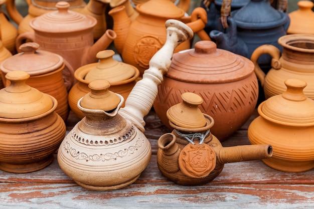 Tazze, pentole e piatti marrone argilla fatti a mano su un supporto di legno