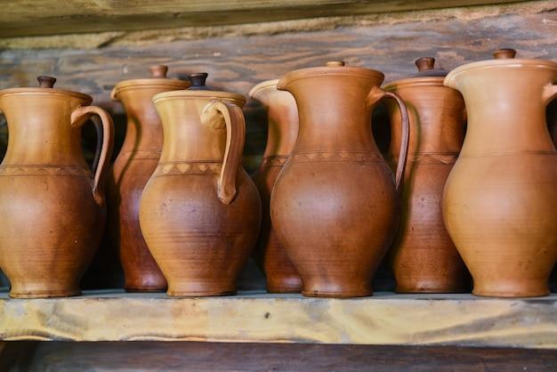 Brocche di argilla fatte a mano sullo scaffale in negozio, primi piani