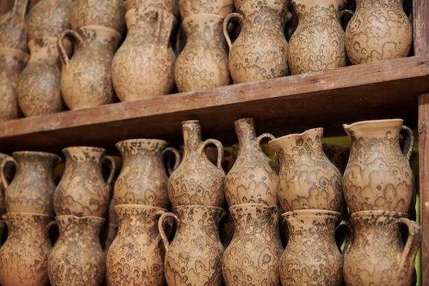Brocche di argilla fatte a mano su uno scaffale in officina