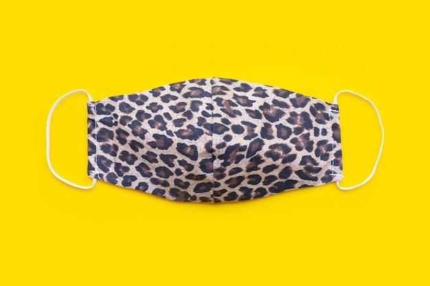 Maschera in stoffa fatta a mano, motivo pelle di tigre. sfondo giallo. vista dall'alto
