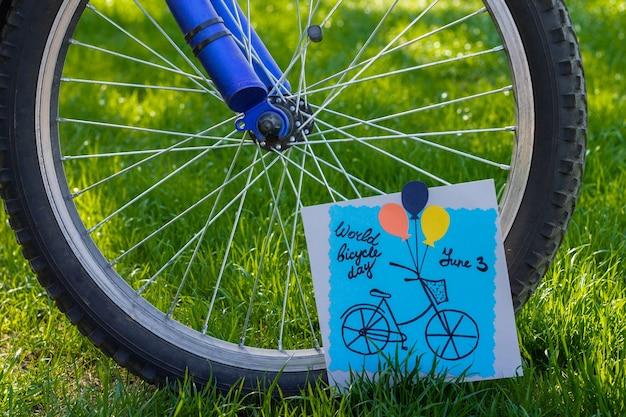 Biglietto di auguri di carta colorata fatta a mano accanto a una ruota di bicicletta su sfondo di erba. fai da te. giornata mondiale della bicicletta.