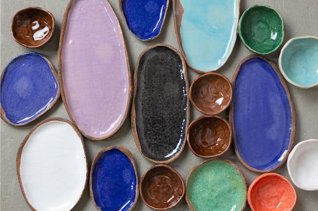 Piatti e piatti vuoti in ceramica colorati fatti a mano sfondo, vista dall'alto. collezioni di varie piccole ciotole su sfondo grigio