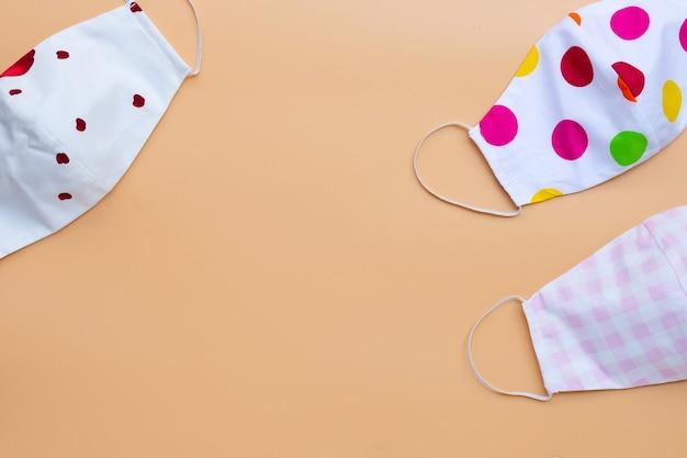 Maschere di stoffa colorate fatte a mano sulla superficie gialla